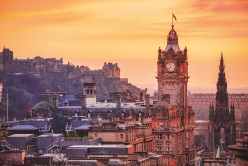 Looking over the buildings and roofs of Edinburgh Old Town towards Edinburgh Castle from Calton Hill as the sun sets.